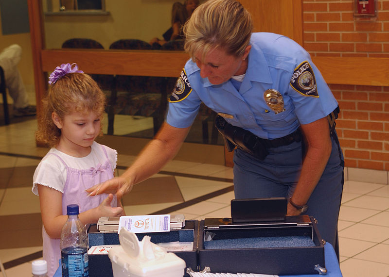 US Navy 060830 N 8907D 010 Officer Diane Branch with the Chesapeake Police Department takes childrens fingerprints during the Ident a Kid program held at Naval Medical Center Portsmouth Are police officers supposed to be scary?
